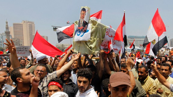 Opponents of Morsy shout slogans as they carry a symbolic coffin during a protest in Tahrir Square on July 3.