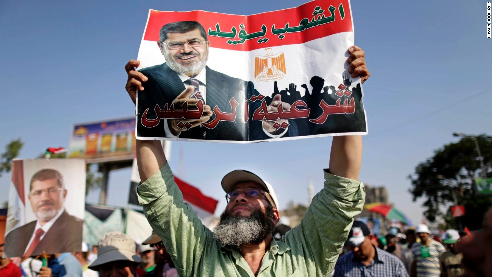 "A supporter of Morsy holds a poster that reads, ""The people support legitimacy for the president,"" during a rally in Cairo on July 3."