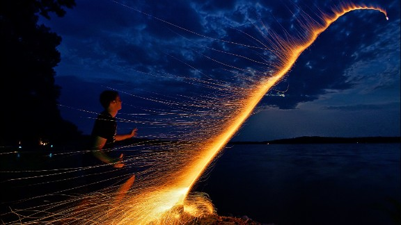 "Dan Anderson managed to capture the moment his nephew launched a bottle rocket across Minnesota's Lake Koronis, during Fourth of July 2012. They had carefully prepared everything to take the perfect photo, counting the seconds it took from lighting the fuse to the explosion of the firework and arranging the camera on a tripod. ""We did it in one take and then ran away because the mosquitoes were eating us alive,"" Anderson says."