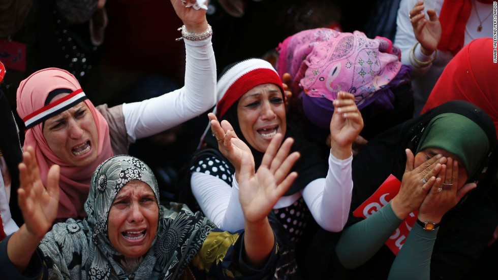 Women react to the flag-draped body of a victim (not pictured) who was killed during fighting outside Cairo University on July 3.