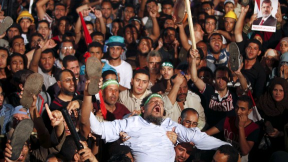 Members of the Muslim Brotherhood and Morsy supporters react at the Raba El-Adwyia mosque square on July 3 after the Egyptian Army