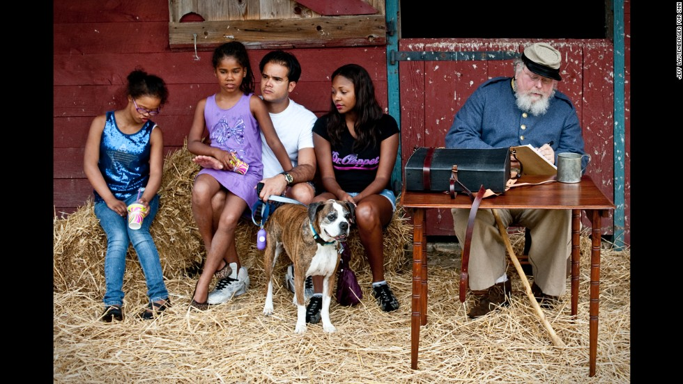 Taylor Babilonia, Morgan Babilonia, Robert Babilonia and Karen Hines, of Washington, and family dog Madison relax as a re-enactor sets up for a period tintype portrait shoot at Daniel Lady Farm on June 28, during the re-enactment of the Battle of Gettysburg.