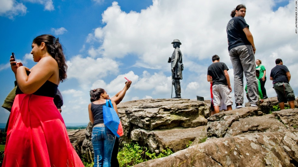 High-schoolers from Philadelphia take photographs of themselves June 11, by the monument to Union Gen. Gouverneur Warren at Little Round Top, a major fighting location during the Battle of Gettysburg.
