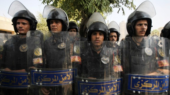 Riot police stand guard as members of the Muslim Brotherhood and supporters of Morsy protest in front of Egypt