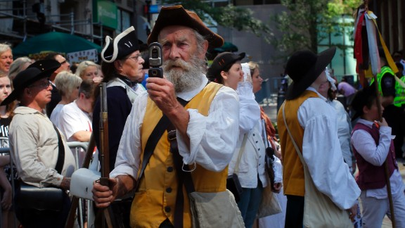 A re-enactor in colonial attire takes a photograph with his mobile phone before a public reading of the Declaration of Independence in Boston.