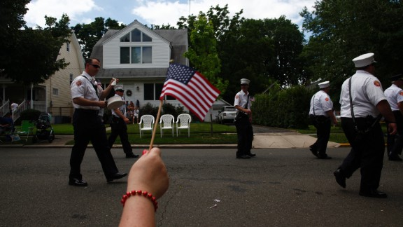 An observer waves an American flag during the parade in Ridgefield Park.