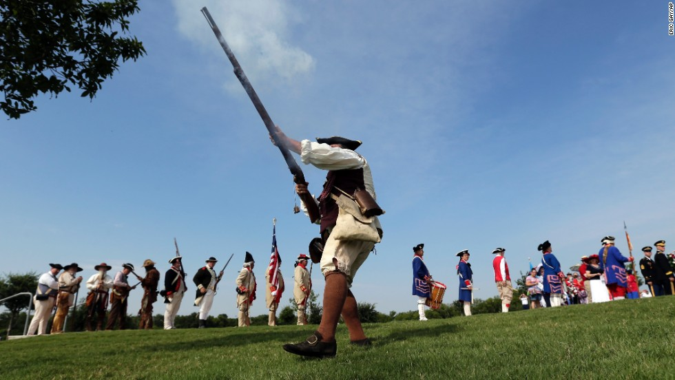 "Ed Lunderman, a member of a Living History Musket Detail, fires his weapon to represent ""the shot heard around the world"" during a Fourth of July ceremony at Fort Sam Houston National Cemetery in San Antonio."