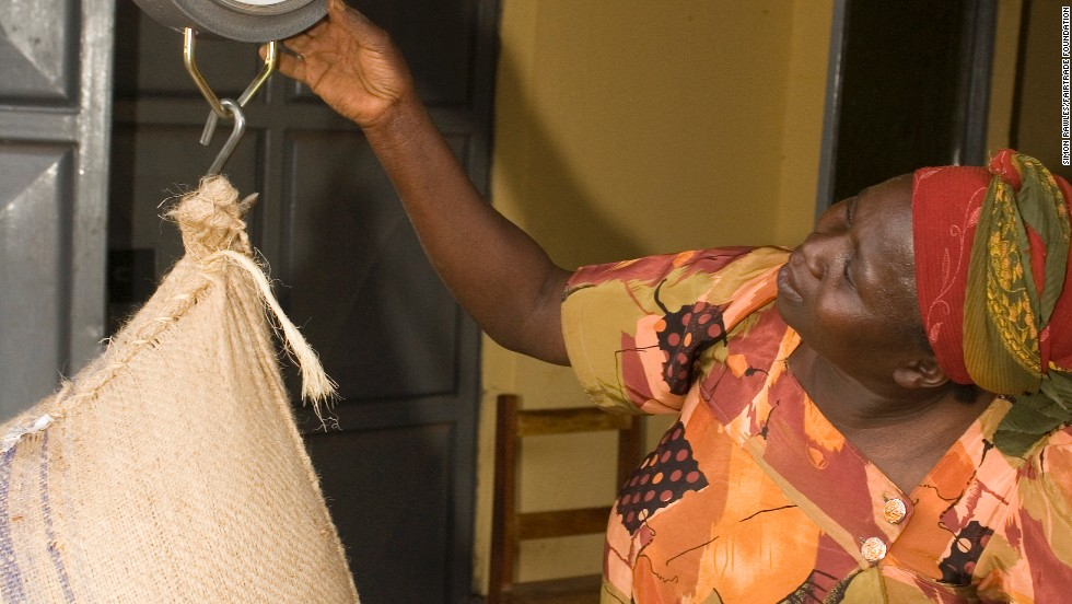 A smallholder coffee farmer in Uganda weighs beans before they are exported and sold
