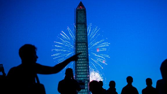 People watch fireworks burst behind the Washington Monument on the National Mall in Washington on Thursday, July 4.