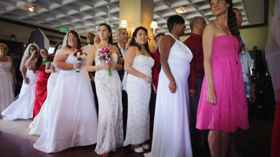 Brides line up with their grooms during a group Valentine's Day wedding at the National Croquet Center on February 14, 2013, in West Palm Beach, Florida. The group wedding is put on by the Palm Beach Country Clerk & Comptroller's office, and approximately 40 couples tied the knot.