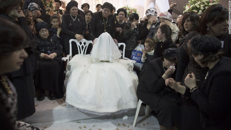 A Jewish Bride Is Surrounded By Relatives During Her Wedding To The Great Grandson Of