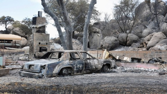 A deadly wildfire leaves behind little but a burned-out car and the remains of a house in a Yarnell, Arizona, neighborhood on Wednesday, July 3. The fire started a week ago near Yarnell, apparently because of lightning strikes. Nineteen firefighters were killed Sunday, June 30, battling the blaze northwest of Phoenix.