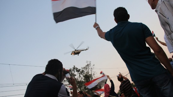 """<a href=""""http://ireport.cnn.com/docs/DOC-999917"""">Norman Halim</a> also captured this striking image earlier July 3 of an army helicopter hovering over the crowd."""