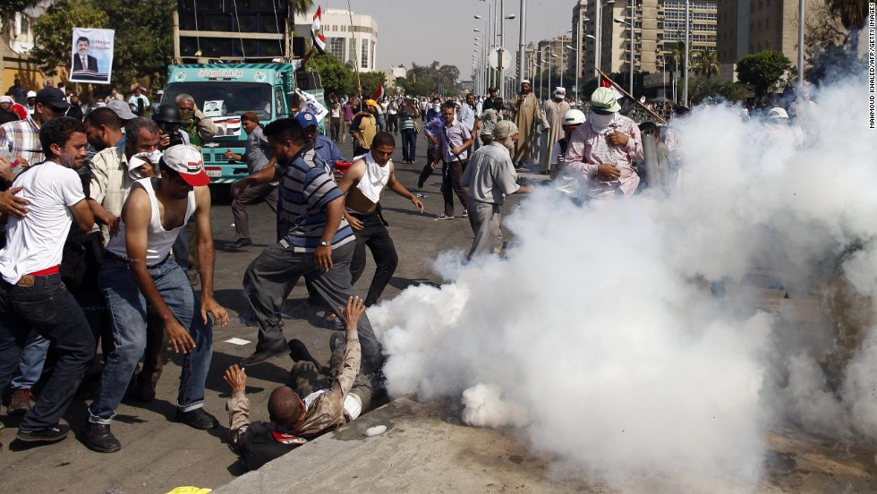 Protesters take cover from tear gas during clashes outside the headquarters of the Republican Guard in Cairo on July 5.