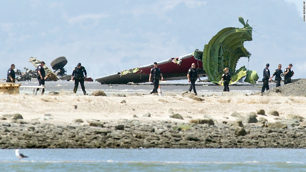 Investigators pass the detached tail and landing gear of Asiana Airlines Flight 214 on July 6.