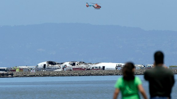 A helicopter flies above the wreckage on July 6 as people observe from across the waters of San Francisco Bay.
