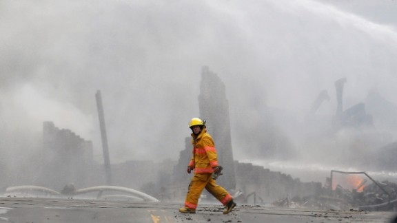 A firefighter walks past the remains of buildings in Lac-Megantic on July 6.