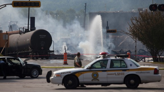 Firefighters continue to douse burning wreckage on July 7 in Lac-Megantic, Quebec.