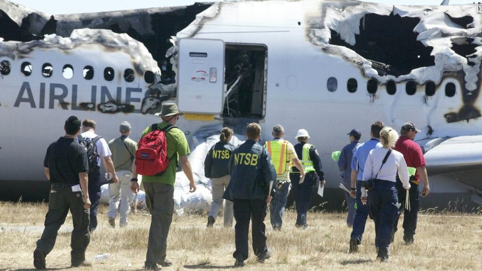 Investigators approach the crash in a handout photo released on July 7.