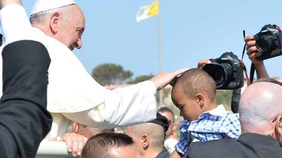 Pope Francis blesses a child as he arrives on the island.