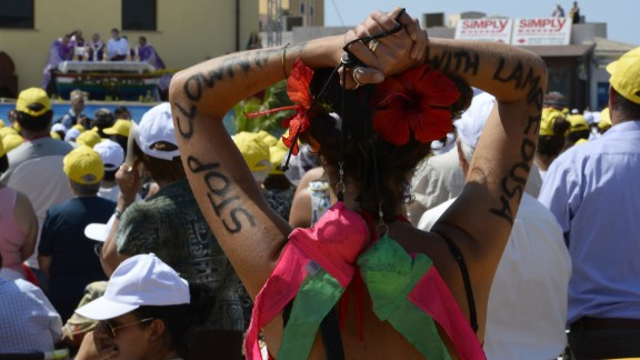 """A faithful has """"Stop clowning with Lampedusa"""" painted on her arms as the pope led  the mass. """"The culture of well-being, that makes us think of ourselves, that makes us insensitive to the cries of others, that makes us live in soap bubbles, that are beautiful but are nothing, are illusions of futility, of the transient, that brings indifference to others, that brings even the globalization of indifference,"""" said Pope Francis."""