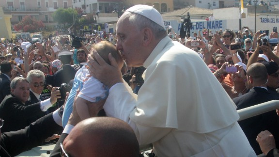 Pope Francis blesses a child. The pontiff thanked the people of Lampedusa along with the rescue workers, NGOs and volunteers who man the centers on the island where refugees are taken.