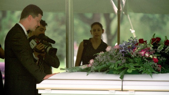 Russell Yates places his hand on the casket of one of his deceased children during their funeral on June 27, 2001, at Forest Park East Cemetery in Houston. On July 30, 2004, he filed for divorce from Andrea.