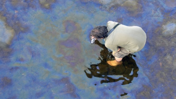 A man collects oil floating on the Chaudiere River near Lac-Megantic on July 8.