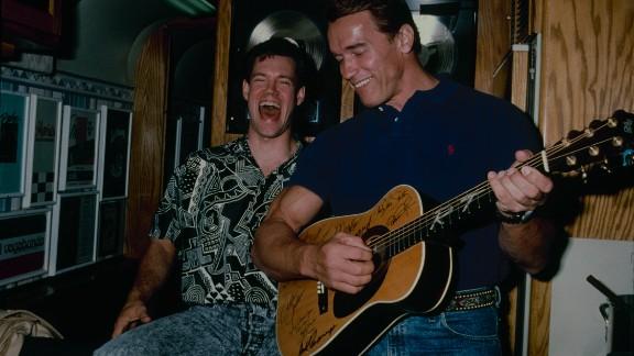 Travis laughs with Arnold Schwarzenegger in 1990.