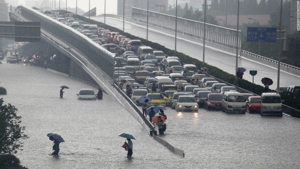 Heavy rains force people to walk across a flooded road and leave vehicles trapped on a viaduct in Wuhan, the capital of Hubei province in central China, on Sunday, July 7.