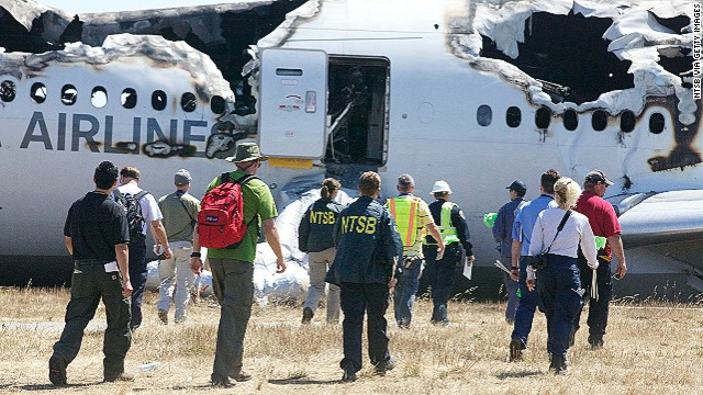 In this handout photo provided by the National Transportation Safety Board, NTSB investigators examine the wreckage of Asiana Airlines flight 214 following yesterday's crash, on July 7, 2013 in San Francisco, California.