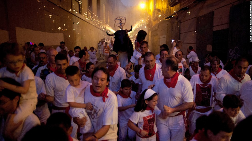 "A flaming bull, or ""toro del fuego,"" is run through the streets on July 9."