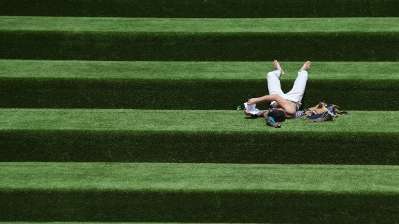 A man reads a book in the sunshine on steps covered in artificial grass on July 10 in London.