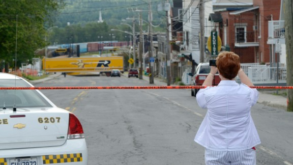 A woman takes a photo of the devastation on Tuesday, July 9.