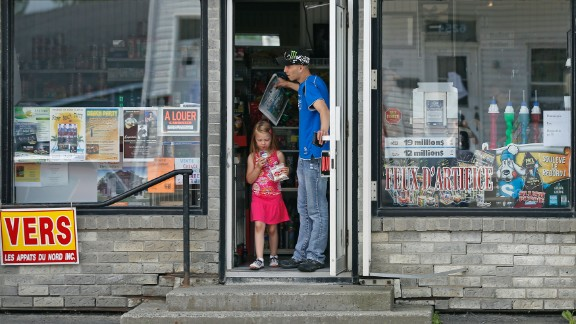 Residents leave a convenience store in a part of Lac Megantic that reopened on July 9.