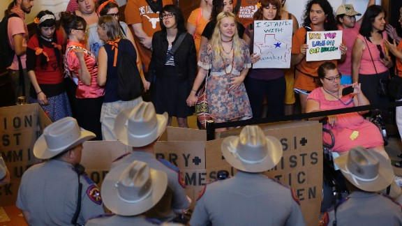 On October 28, 2013, the day before the legislation was scheduled to take effect, a federal judge ruled that parts of it were unconstitutional. Above, state troopers look on as a group in Austin, Texas, protests the law.