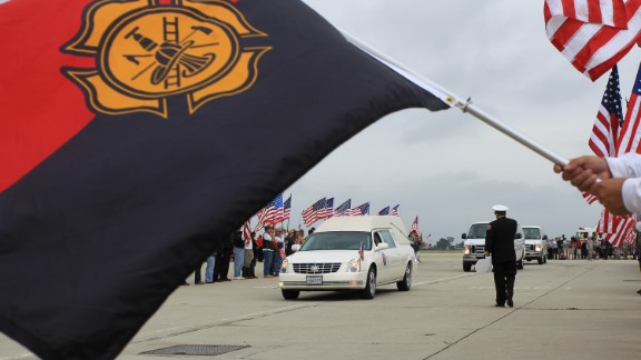 A hearse carrying the body of Christopher MacKenzie arrives at Los Alamitos Air Field, California, on July 10. MacKenzie was one of the 19 firefighters who lost their lives when they became trapped and their position overrun by flames from the Yarnell Hill Fire, southwest of Prescott on June 30.