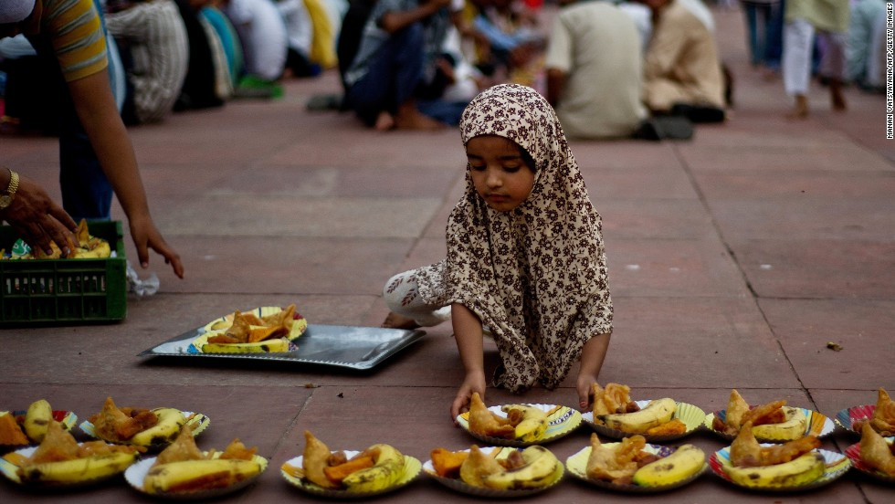 A young Muslim girl arranges food plates before Iftar, the evening meal when Muslims break their fast, at the Jama Masjid mosque in New Delhi on July 11.