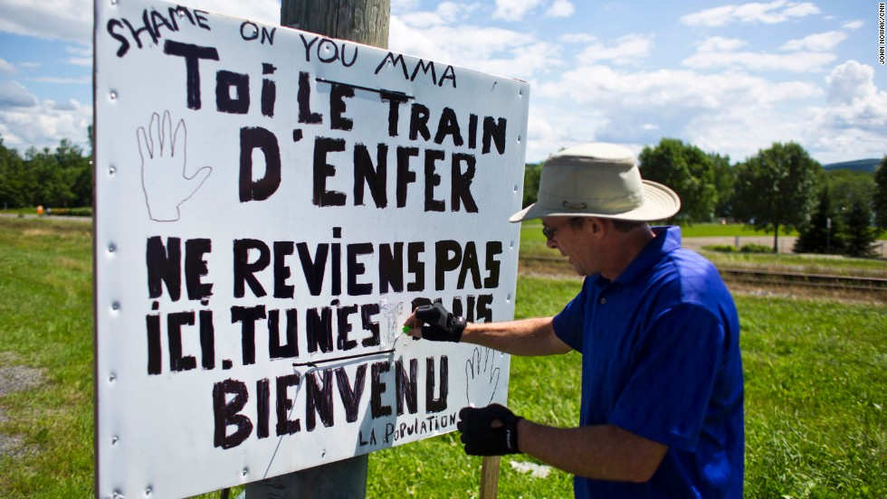 "Andre Blais adjusts a sign erected near the train tracks. It bears a message for the rail company: ""Shame on you MMA.""  It is signed ""The population"" and refers to the ""train from hell."""