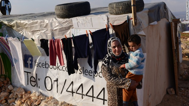 A woman refugee holds her son outside a tent shelter in a makeshift encampment in the Bekaa Valley of Lebanon.