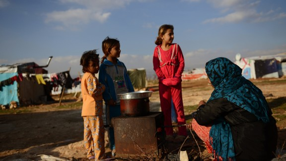 A woman prepares a meal outdoors in a makeshift refugee camp in Lebanon.