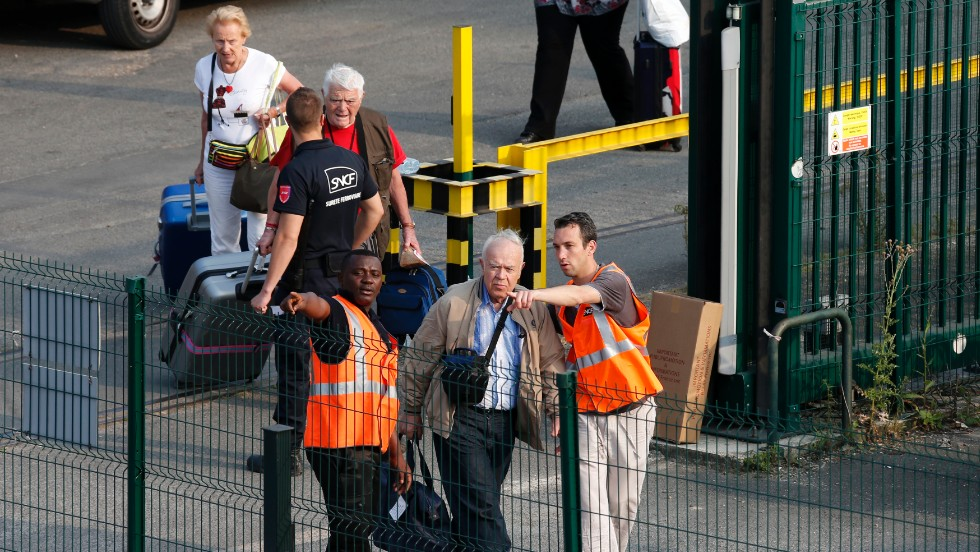 Passengers are escorted from the scene by French railway employees on July 12.