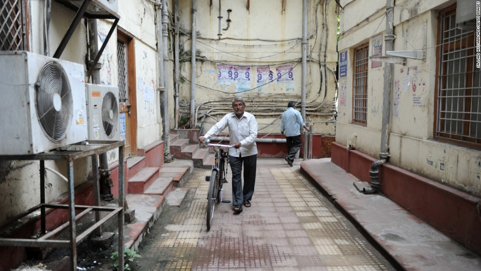 Indian telegram messenger Om Dutt, 56, wheels his bicycle at the Central Telegraph Office in New Delhi. BSNL said their telegram messengers will be transferred to their landline, mobile and broadband departments.