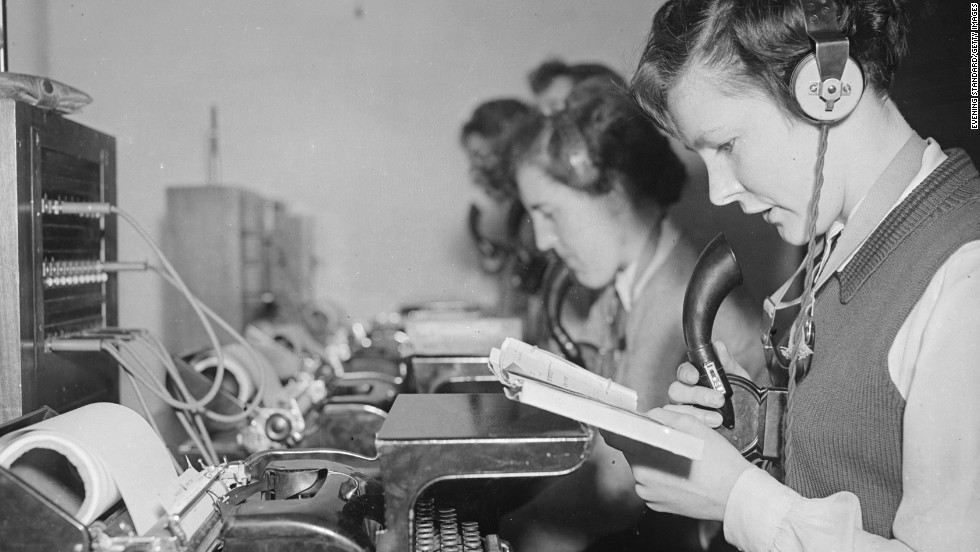 General Post Office workers circa 1952 transmit and receive telegram messages over the phone, transcribing them directly by means of a typewriter.