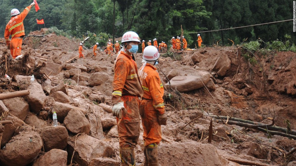 Rescuers work at the site of a massive landslide in Dujiangyan in southwest China's Sichuan province on Friday, July 12. The landslide killed at least 43 people and left 118 missing. The flooding that triggered the landslide has affected 1.5 million people and inundated tens of thousands of acres of crops.