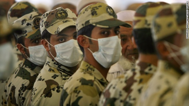 Saudi policemen, wearing protective masks against swine flu, stand guard near the holy city of Mecca on November 28, 2009.