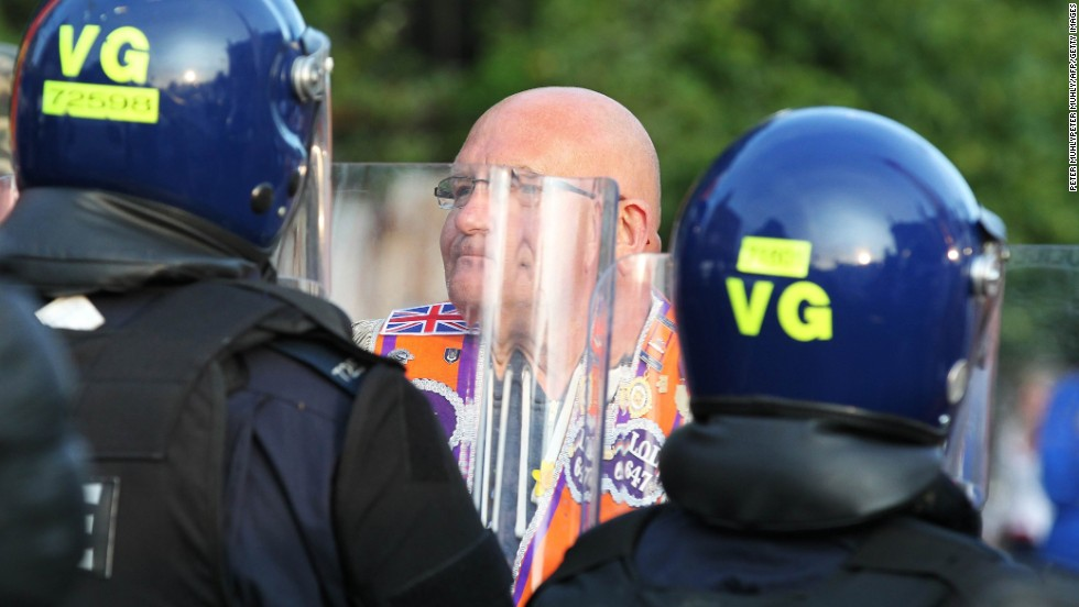 A man confronts riot police as a small protest is stopped along Shankill Road in Belfast on July 13. The Friday night protests left 32 police officers injured and required hundreds of additional officers to be sent in from Britain.