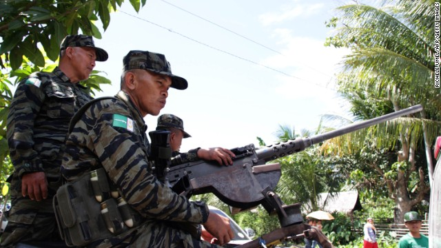 Rebels stand guard on February 11 during the visit of Philippine President Benigno Aquino to the rebels' stronghold in Mindanao.