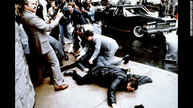 This photo taken by presidential photographer Mike Evens on March 30, 1981 shows police and Secret Service agents reacting during the assassination attempt on then US president Ronald Reagan, after a conference outside the Hilton Hotel in Washington, D.C.. Police officer Thomas Delahanty (foreground) and Press Secretary James Brady (behind) lay wounded on the ground. Reagan was hit by one of six shots fired by John Hinckley, who also seriously injured press secretary James Brady (just behind the car).  Reagan was hit in the chest and was hospitalized for 12 days. Hinckley was aquitted 21 June 1982 after a jury found him mentally unstable. (Photo credit should read MIKE EVENS/AFP/Getty Images)