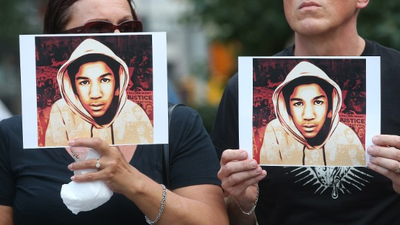 People hold photos of Trayvon Martin at a rally in Manhattan